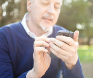 Senior man using his cell phone Stock Photo