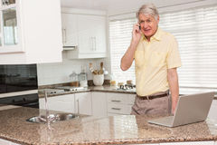 Senior man using his laptop on the phone Royalty Free Stock Photos