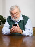 Retiree and his smart phone Royalty Free Stock Photography