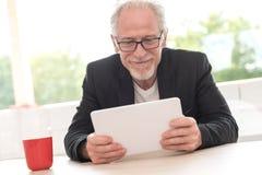 Senior man using his tablet. At home Royalty Free Stock Image