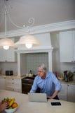 Senior man using interacting while using laptop in kitchen Stock Images