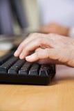 Senior Man Using Keyboard In Computer Class Stock Photo
