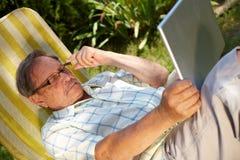 Senior man using laptop  Stock Images