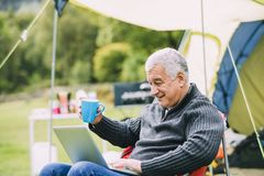 Senior man Using Laptop at Campsite. Senior man is relaxing in a chair by his tent in the campsite. He is enjoying a cup of tea while using a laptop stock images