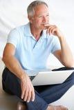 Senior man using laptop computer. Thinking Stock Photo
