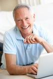 Senior man using laptop computer. Smiling Royalty Free Stock Images