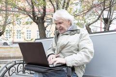 Senior man using laptop computer outdoors Royalty Free Stock Images