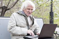 Senior man using laptop computer outdoors Royalty Free Stock Photo