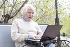 Senior man using laptop computer outdoors Stock Photos
