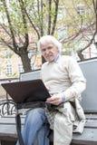Senior man using laptop computer outdoors Royalty Free Stock Image