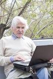 Senior man using laptop computer outdoors Royalty Free Stock Photography