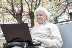 Senior man using laptop computer outdoors Stock Photo
