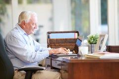 Senior Man Using Laptop On Desk At Home Royalty Free Stock Image