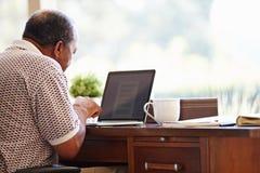 Senior Man Using Laptop On Desk At Home Stock Photo