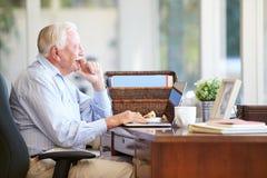 Senior Man Using Laptop On Desk At Home Stock Photos