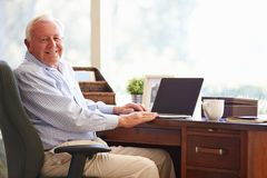 Senior Man Using Laptop On Desk At Home Royalty Free Stock Photo