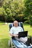 Senior man using laptop in garden Royalty Free Stock Image