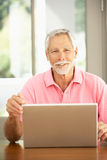 Senior Man Using Laptop At Home Stock Photo