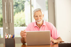 Senior Man Using Laptop At Home. Senior Man Using A Laptop At Home Royalty Free Stock Images