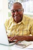 Senior Man Using Laptop At Home Royalty Free Stock Photos