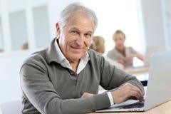 Senior man using laptop in informatics course Stock Image
