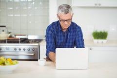 Senior man using laptop in kitchen Stock Image