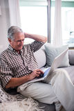 Senior man using laptop in living room Stock Photography
