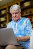 Senior man using laptop in living room Royalty Free Stock Images