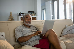 Senior man using laptop in the living room Royalty Free Stock Photos