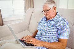 Senior man using laptop in living room Royalty Free Stock Photography