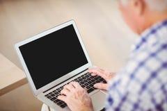 Senior man using laptop in living room Stock Photos