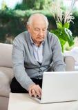 Senior Man Using Laptop At Nursing Home Porch Royalty Free Stock Images
