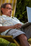 Senior man using laptop outdoor Royalty Free Stock Photos