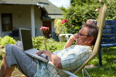 Senior man using laptop outdoor Stock Photo