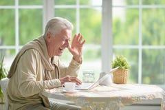 Senior man using laptop Stock Photo