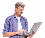 Senior man. Is using laptop, standing on white background stock images