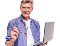 Senior man. Is using laptop, standing on white background royalty free stock photography