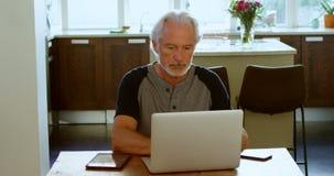 Senior man using laptop on table 4k stock video footage