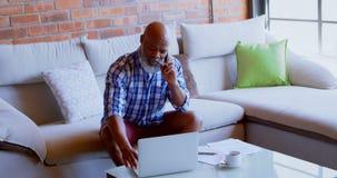Senior man using laptop while talking om mobile phone in living room 4k. Senior man using laptop while talking om mobile phone in living room at home 4k