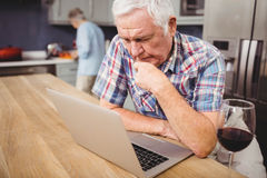 Senior man using laptop and woman working in kitchen Royalty Free Stock Photography