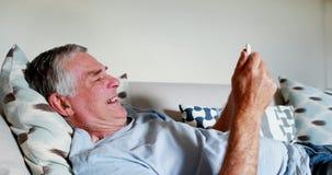 Senior man using mobile phone in bedroom 4k stock video footage