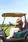 Senior man using mobile phone and driving cart. Looking busy. Portrait of senior man sidewise using mobile phone and driving cart on course Stock Images