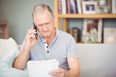 Senior man using mobile phone while looking documents Royalty Free Stock Photos