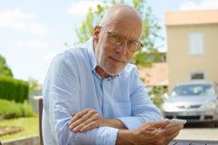 Senior man using the mobile phone outside Stock Photo