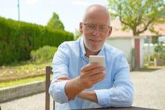 Senior man using the mobile phone outside Royalty Free Stock Photo