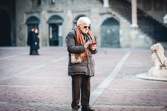 Senior man is using mobile phone at street of Bergamo town, Italy Stock Photos