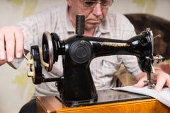 Senior Man Using Old Fashioned Sewing Machine Stock Images