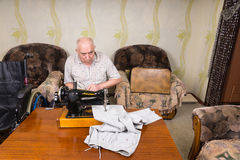 Senior Man Using Old Fashioned Sewing Machine Royalty Free Stock Photography