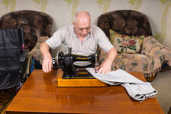 Senior Man Using Old Fashioned Sewing Machine Royalty Free Stock Photo