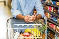Senior man using phone at grocery store Royalty Free Stock Image